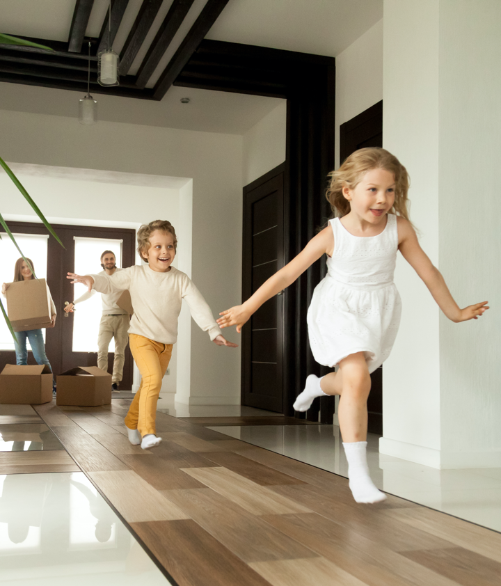 Excited children running into big modern house with parents in the background