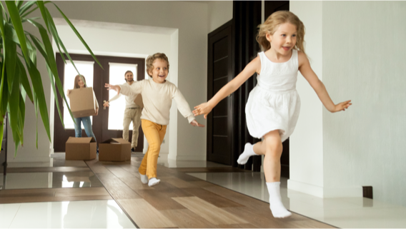 Excited children running into big modern house with parents in the background (small image)