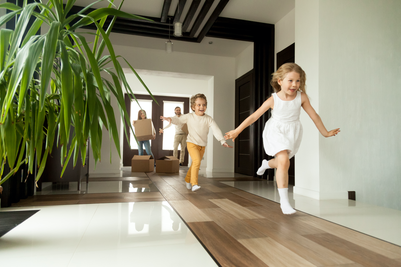 Excited children running into big modern house with parents in the background (large image)